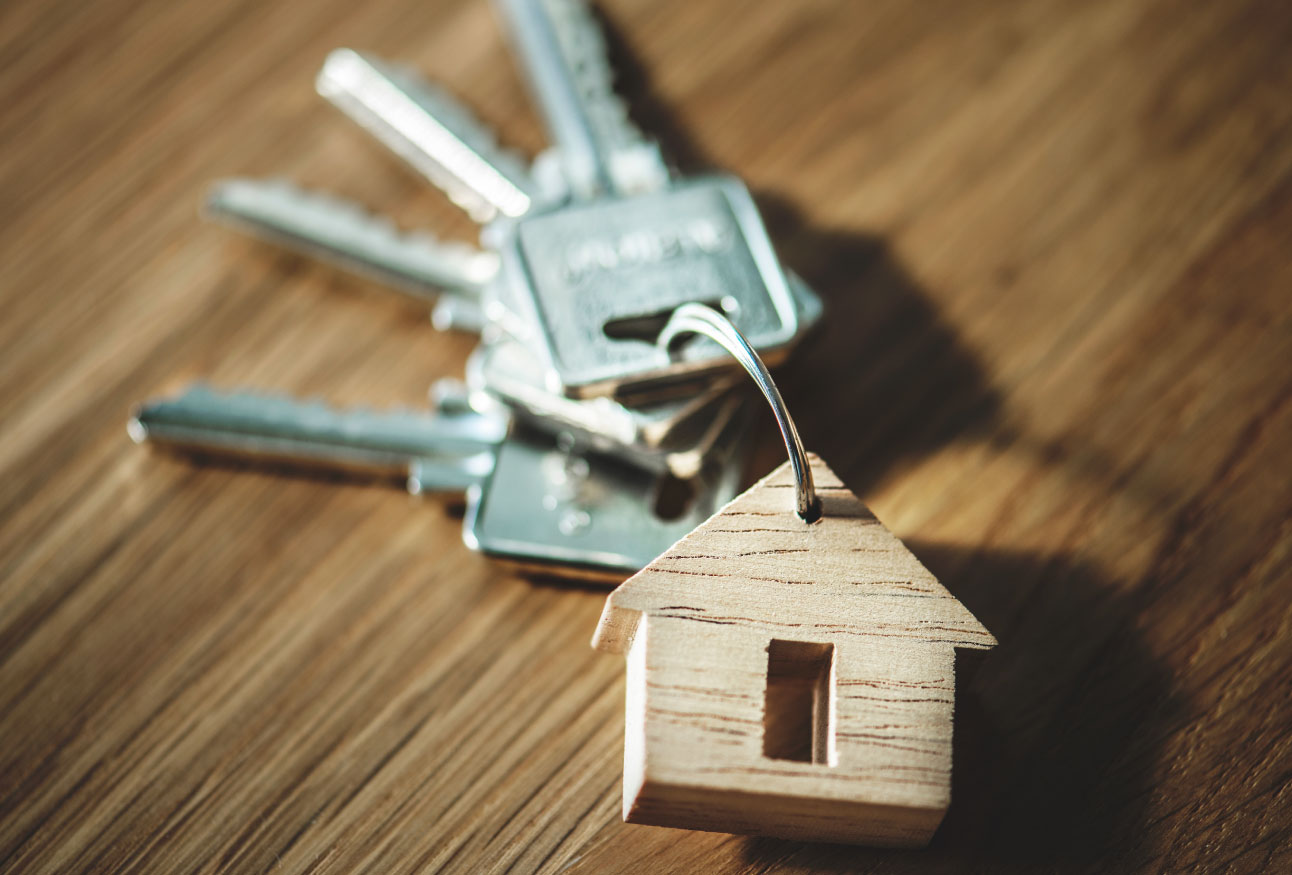 Set of keys on wood table with small wooden house keychain