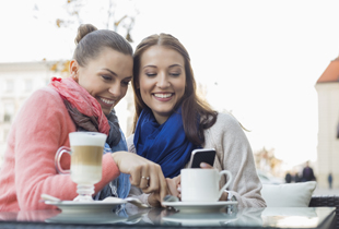 Two female friends at restaurant looking at phone