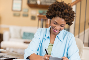 Woman smiling while she writes a check