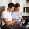 Smiling couple sitting on floor using tablet